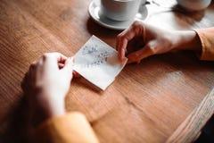 Τα θηλυκά χέρια προσώπων κρατούν τη σημείωση αγάπης Στοκ Εικόνες