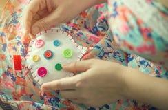 Τα θηλυκά χέρια ράβουν την άσπρη καρδιά βαμβακιού με τα διαφορετικά χρώματα κουμπιών Χειροποίητος η έννοια της αγάπης Valentine&  Στοκ Εικόνες