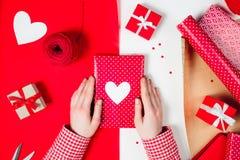 Τα θηλυκά χέρια τυλίγουν ένα δώρο βαλεντίνων στο κόκκινο Στοκ φωτογραφίες με δικαίωμα ελεύθερης χρήσης