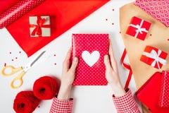 Τα θηλυκά χέρια τυλίγουν ένα δώρο βαλεντίνων στο κόκκινο Στοκ Εικόνες