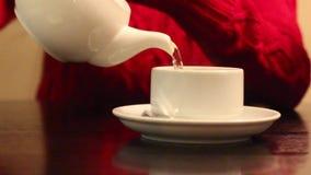 Τα θηλυκά χέρια χύνουν το καυτό τσάι στο άσπρο φλυτζάνι στον πίνακα στον καφέ, ρηχό dof απόθεμα βίντεο