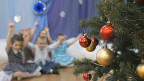Τα θολωμένα παιδιά που κυματίζουν δίνουν κοντά στο χριστουγεννιάτικο δέντρο απόθεμα βίντεο