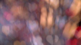 Τα θολωμένα πολύχρωμα φω'τα με μορφή ενός εορτασμού καρδιών αφαιρούν το ντεκόρ, λαμπρό υπόβαθρο bokeh απόθεμα βίντεο