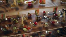 Τα διάφορα πρόχειρα φαγητά σε έναν πίνακα μπουφέδων στο γεγονός, η κάμερα κινούνται ομαλά φιλμ μικρού μήκους