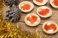 Τα διάφορα tartlets με το κόκκινο χαβιάρι και τη βουτύρου tinsel άποψη επιτραπέζιων κορυφών έλατου coneson ξύλινη καφετιά Στοκ Φωτογραφία
