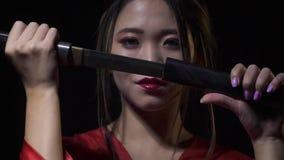 Τα ιαπωνικά γκέισα βγάζουν ένα μαχαίρι με ένα χαμόγελο, που εμφανίζεται από το σκοτεινό, σε αργή κίνηση απόθεμα βίντεο
