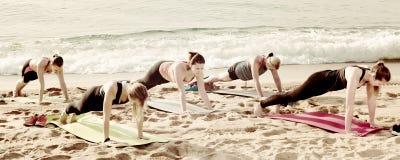 Τα ικανοποιημένα θηλυκά που ασκούν τη γιόγκα θέτουν στην ηλιόλουστη παραλία Στοκ φωτογραφίες με δικαίωμα ελεύθερης χρήσης