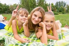 Τα κέρατα Mom και προσφερθείς δύο κόρες και μια διασκέδαση εξετάζουν το πλαίσιο στοκ εικόνες