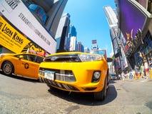 Τα κίτρινα αμάξια και το νέο ανάβουν κατά περιόδους το τετράγωνο στην πόλη της Νέας Υόρκης Στοκ Εικόνα