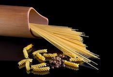 Τα κίτρινα ιταλικά ζυμαρικά, μακαρόνια, μαύρο πιπέρι που απομονώθηκε ενάντια στο Μαύρο απομόνωσαν το υπόβαθρο Μια όμορφη ακόμα ζω στοκ εικόνες