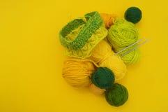 Τα κίτρινα και πράσινα παλτά του μαλλιού βρίσκονται στον πίνακα Το αγαπημένο χόμπι πλέκει στοκ φωτογραφίες