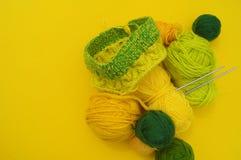 Τα κίτρινα και πράσινα παλτά του μαλλιού βρίσκονται στον πίνακα Το αγαπημένο χόμπι πλέκει στοκ εικόνα με δικαίωμα ελεύθερης χρήσης