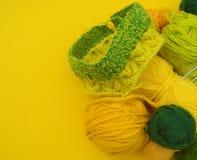 Τα κίτρινα και πράσινα παλτά του μαλλιού βρίσκονται στον πίνακα Το αγαπημένο χόμπι πλέκει στοκ εικόνες