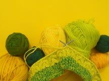 Τα κίτρινα και πράσινα παλτά του μαλλιού βρίσκονται στον πίνακα Το αγαπημένο χόμπι πλέκει στοκ εικόνες με δικαίωμα ελεύθερης χρήσης