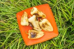 Τα κίτρινα πιπέρια τηγάνισαν σε μια σχάρα σε ένα πορτοκαλί πιάτο ενάντια σε μια πλάτη Στοκ φωτογραφία με δικαίωμα ελεύθερης χρήσης