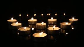 Τα καίγοντας κεριά καίγοντας κεριά ενός στα μαύρα καθρεφτών υποβάθρου θα εξασθενίσουν ταυτόχρονα μακριά απόθεμα βίντεο