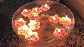 Τα καίγοντας κεριά με μορφή ενός λουλουδιού επιπλέουν στο νερό απόθεμα βίντεο