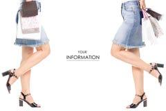 Τα καθορισμένα θηλυκά πόδια στο μαύρο τζιν παπουτσιών περιζώνουν το διαθέσιμο χέρι τοποθετούν το σχέδιο πώλησης αγορών σε σάκκο Στοκ εικόνες με δικαίωμα ελεύθερης χρήσης