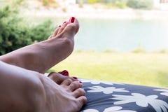 Τα καλά φροντισμένα πόδια της τοποθέτησης γυναικών ηλιοθεραπείας στη γέφυρα προεδρεύουν κοντά επάνω με το υπόβαθρο φύσης στοκ φωτογραφίες