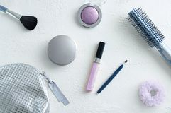 Τα καλλυντικά σε ένα άσπρο τραχύ υπόβαθρο, makeup βούρτσα για τη σκόνη προσώπου, χείλι σκιών ματιών σχολιάζουν την τρίχα στοκ φωτογραφία με δικαίωμα ελεύθερης χρήσης