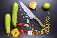 Τα καλύτερα συστατικά είναι ο αρχιμάγειρας αρχιμαγείρων ` s Στα μαύρα κεραμικά επιτραπέζια λαχανικά, το μαχαίρι και τα καρυκεύματ Στοκ Εικόνες
