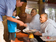 τα καμποτζιανά παιδιά ενηλίκων δίνουν τα χρήματα Στοκ Εικόνα