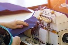 Τα κατάλληλα χέρια ράβουν τα υφάσματα στη ράβοντας μηχανή Στοκ Φωτογραφία