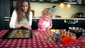 Τα καλά μπισκότα μπισκότων θέσεων μητέρων και κορών στο φούρνο καλύπτουν τον κασσίτερο στην κουζίνα απόθεμα βίντεο