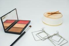 τα καλλυντικά, αποτελούν τη βούρτσα και τη σκόνη και με τα σκουλαρίκια για τις γυναίκες Στοκ Φωτογραφία