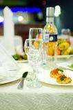 Τα κενά γυαλιά κρασιού για τα οινοπνευματώδη ποτά και τα πρόχειρα φαγητά στέκονται στον εξυπηρετούμενο πίνακα στοκ εικόνα
