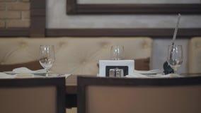 Τα κενά γυαλιά, πιάτα, δίκρανο, μαχαίρι εξυπηρέτησαν για το γεύμα στο εστιατόριο με το άνετο εσωτερικό Επιτραπέζια εξυπηρέτηση απόθεμα βίντεο