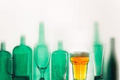 Τα κενά πράσινα μπουκάλια γυαλιού και ένα ποτήρι της μπύρας στέκονται στην έννοια ποτών σειρών Στοκ φωτογραφία με δικαίωμα ελεύθερης χρήσης