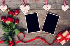 Τα κενά πλαίσια φωτογραφιών, κόκκινα τριαντάφυλλα ανθίζουν, κόκκινα κορδέλλα και κιβώτιο δώρων Στοκ Εικόνες