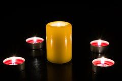 Τα κεριά ανάβουν στον πίνακα, σκοτεινό υπόβαθρο Στοκ Εικόνες