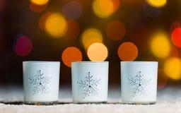 Τα κεριά που στέκονται στο χιόνι με τα φω'τα νεράιδων, το πορτοκαλί ή χρυσό bokeh στο υπόβαθρο Στοκ εικόνες με δικαίωμα ελεύθερης χρήσης