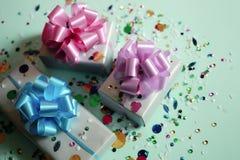 Τα κιβώτια δώρων σε ένα μπλε εορταστικό υπόβαθρο με τα σπινθηρίσματα Στοκ Φωτογραφία