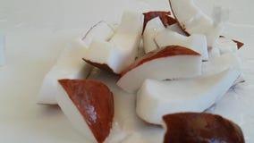 Τα κομμάτια καρύδων στην άσπρη πτώση, εύγευστη, νερό χύνουν φιλμ μικρού μήκους