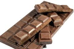 Τα κομμάτια της σοκολάτας συσσώρευσαν επάνω στο φραγμό σοκολάτας που απομονώθηκε στο λευκό Στοκ Εικόνα