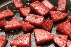 Τα κομμάτια του λουκάνικου είναι τηγανισμένα στο πετρέλαιο σε ένα τηγανίζοντας τηγάνι Στοκ Φωτογραφίες