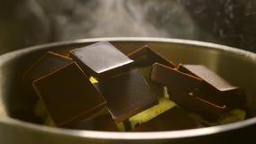 Τα κομμάτια του φραγμού και του βουτύρου σοκολάτας που λειώνουν σε ένα δοχείο, κλείνουν επάνω το βίντεο φιλμ μικρού μήκους