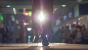 Τα κομψά θηλυκά πρότυπα στα κοστούμια περπατούν το στενό διάδρομο κατά τη διάρκεια της επίδειξης μόδας στο φωτισμό θολωμένο στο υ φιλμ μικρού μήκους