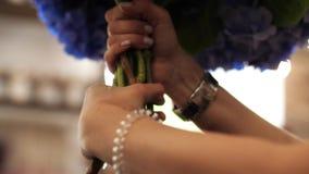 Τα κομψά θηλυκά χέρια στρίβουν μια πολυτελή ανθοδέσμη των μπλε λουλουδιών απόθεμα βίντεο