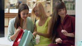 Τα κορίτσια αγοραστών στα ενδύματα εξετάζουν τις αγορές τους στις συσκευασίες μετά από την ημέρα αγορών απόθεμα βίντεο