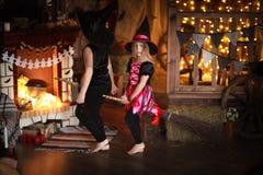 Τα κορίτσια αδελφών μαγεύουν με τη σκούπα αποκριές Στοκ Φωτογραφίες