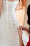 Τα κορίτσια βοηθούν στη νύφη να κουμπώσουν το γαμήλιο φόρεμα Στοκ εικόνες με δικαίωμα ελεύθερης χρήσης