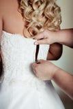 Τα κορίτσια βοηθούν στη νύφη να κουμπώσουν το γαμήλιο φόρεμα Στοκ Φωτογραφίες