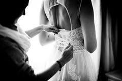 Τα κορίτσια βοηθούν στη νύφη να κουμπώσουν το γαμήλιο φόρεμα Στοκ φωτογραφία με δικαίωμα ελεύθερης χρήσης