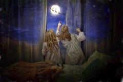 Τα κορίτσια βλέπουν Άγιο Βασίλη από το παράθυρο Στοκ Φωτογραφίες