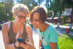Τα κορίτσια εξετάζουν το τηλέφωνο Στοκ φωτογραφία με δικαίωμα ελεύθερης χρήσης
