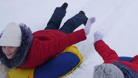 Τα κορίτσια εφήβων κυλούν στο γύρο ελκήθρων κατά μήκος του λευκού σαν το χιόνι δρόμου το χειμώνα Οι φίλες οδηγούν το πιατάκι χιον απόθεμα βίντεο